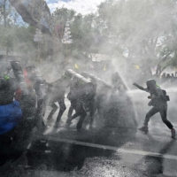 Pro-democracy protesters confront riot police in Bangkok on July 18. | AFP-JIJI