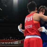 Japan's Sena Irie and the Philippines' Nesthy Petecio embrace after their gold medal bout.  | AFP-JIJI