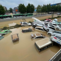 Cars are swept away floodwaters in the city of Zhengzhou, in China's central Henan province, on July 21.   AFP-JIJI