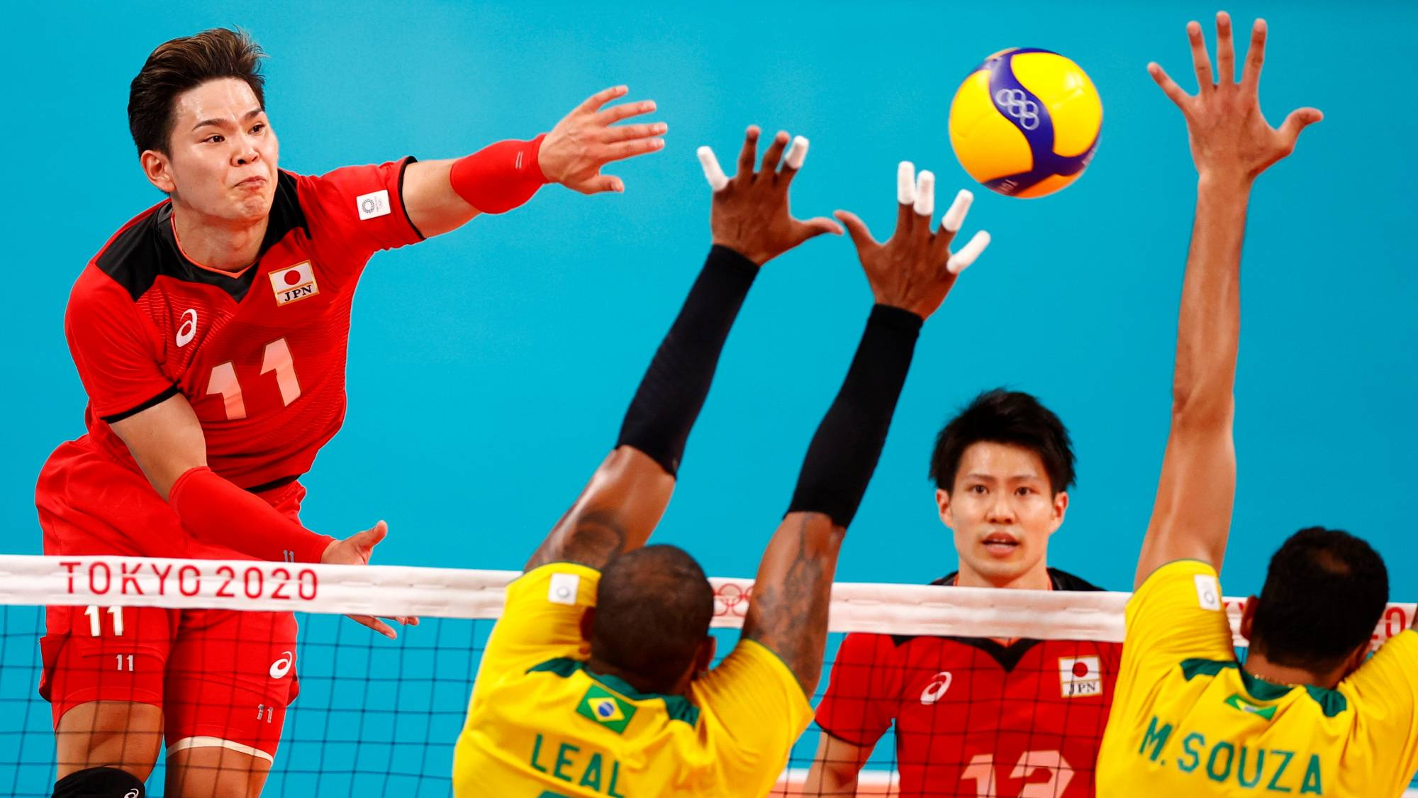 Yuji Nishida of Japan hits the ball as Brazil's Leal and Mauricio Souza go up for a block during their men's quarterfinal match on Tuesday.    REUTERS