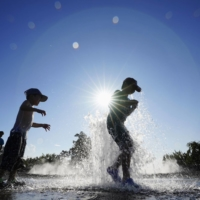 Children cool off in a water park in Isesaki, Gunma Prefecture, as the temperature there hits 40.5 degrees Celsius. Extreme heat alerts have become commonplace for Tokyo in the summer months, too.  | KYODO