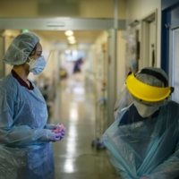 Nao Watarumi (left) waits to remove her protective gear as Junko Yamaguchi does so after emerging from the room of a severely ill COVID-19 patient in the intensive care unit of Itabashi Hospital. | RYUSEI TAKAHASHI