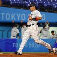 Munetaka Murakami crosses home plate to score Japan's first run against South Korea during their semifinal contest on Wednesday. | REUTERS