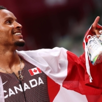 Andre De Grasse of Canada holds his spikes after winning gold in the men's 200 meters at the National Stadium in Tokyo on Wednesday. | REUTERS