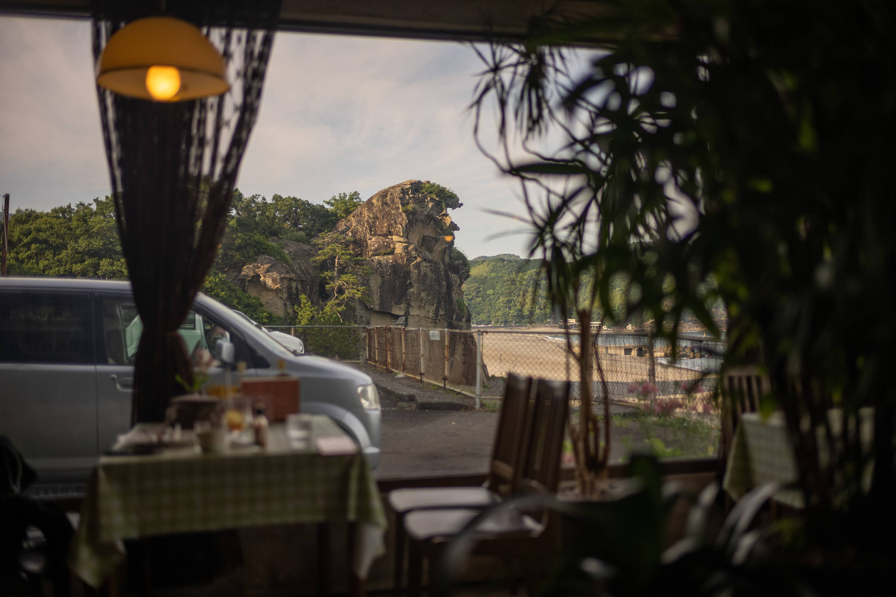 """The 25-meter-tall coastal Shishi-iwa (""""Lion Rock""""), visible through the picture window at Sanchago, a kissaten in Kumano, Mie Prefecture. 