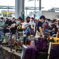 People check in for a flight to the U.K. at Hong Kong International Airport in July.  | AFP-JIJI