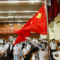 Students attend a flag raising ceremony on National Security Education Day at a secondary school in Hong Kong in April.  | REUTERS