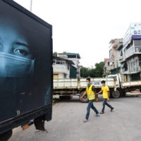 Local residents walk past a make-shift barricade of parked trucks to stop unauthorized travel in Hanoi on July 30 amid a government-imposed two-week lockdown to stop the spread of the coronavirus.   AFP-JIJI