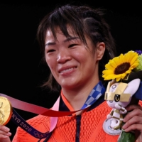 Risako Kawai holds up her gold medal.  | REUTERS