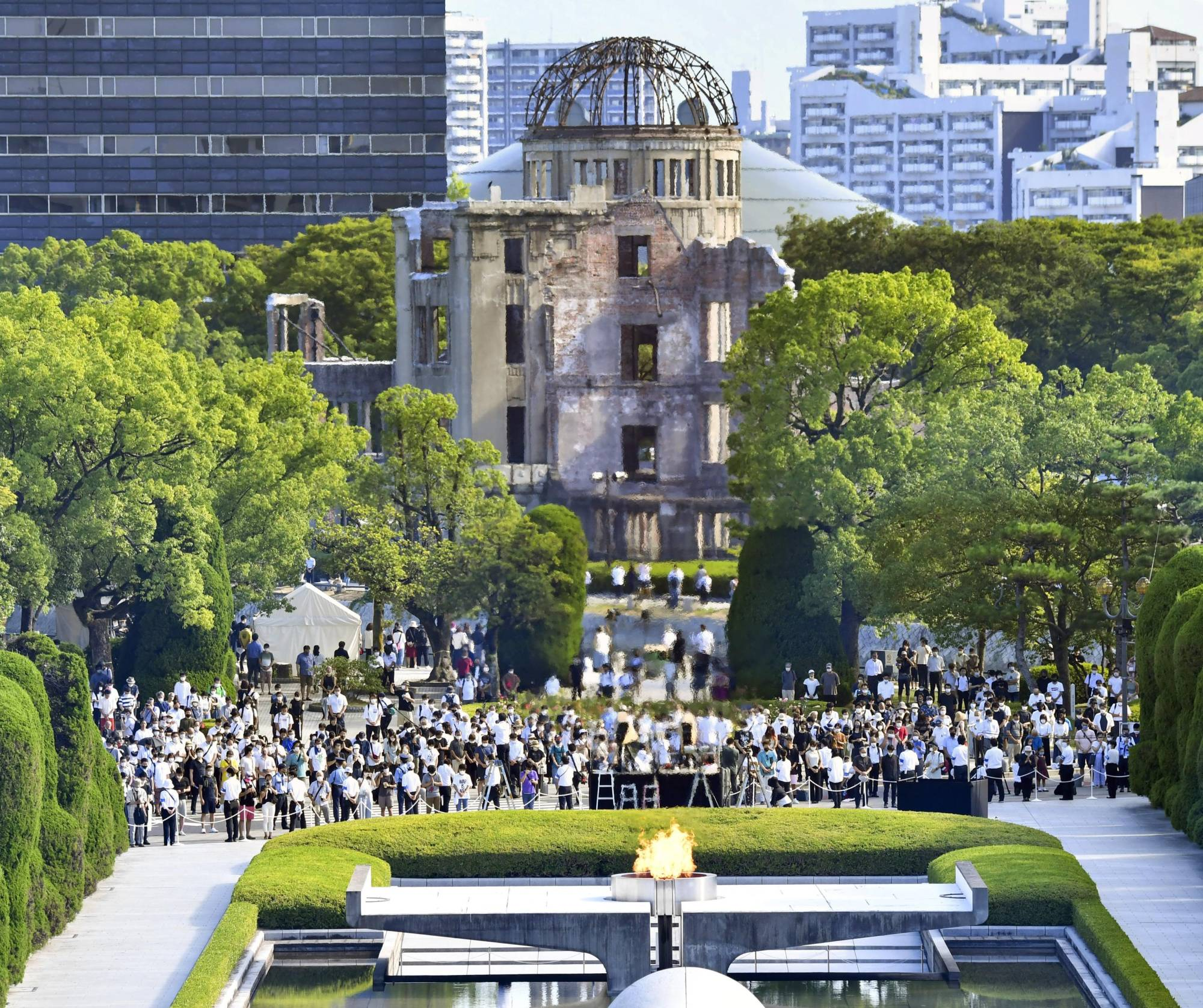 People observe a moment of silence at 8:15 a.m., the time when an atomic bomb was dropped on Hiroshima 76 years ago, at the Peace Memorial Park on Friday.   KYODO