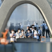 People pray at a monument at the Peace Memorial Park near ground zero in Hiroshima on Friday.   KYODO
