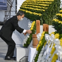 Prime Minister Yoshihide Suga places flowers during the 76th anniversary of the atomic bombing on Hiroshima at the Peace Memorial Park on Friday.   KYODO