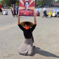A protester holds up a sign calling for the release of Aung San Suu Kyi during a demonstration against the military coup in Naypyidaw in February.  | AFP-JIJI