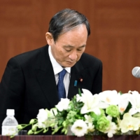 Prime Minister Yoshihide Suga bows at the outset of a news conference in Hiroshima on Friday. | POOL / VIA KYODO