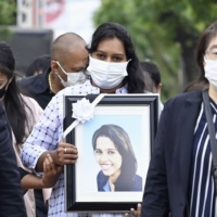 A family member of Ratnayake Liyanage Wishma Sandamali, holding a portrait of her, walks with supporters to the Nagoya Regional Immigration Services Bureau in Aichi Prefecture on May 17. | KYODO