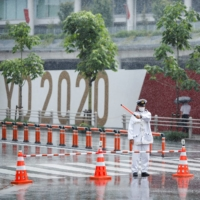 Policemen control the traffic in front of the Olympic stadium in the rain caused by tropical storm Nepartak in Tokyo on July 27. Another tropical storm is approaching the capital on Sunday. | REUTERS