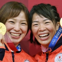Yukako Kawai (left) and her sister, Risako, display the wrestling gold medals they won on Wednesday and Thursday, respectively.  | KYODO