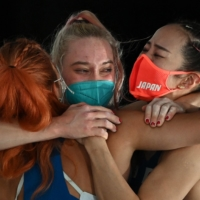 Gold medalist Janja Garnbret (center) hugs silver medalist Miho Nonaka (left) and bronze medalist  Akiyo Noguchi after competing in the women's sport climbing lead final at Aomi Urban Sports Park in Tokyo on Friday.   AFP-JIJI