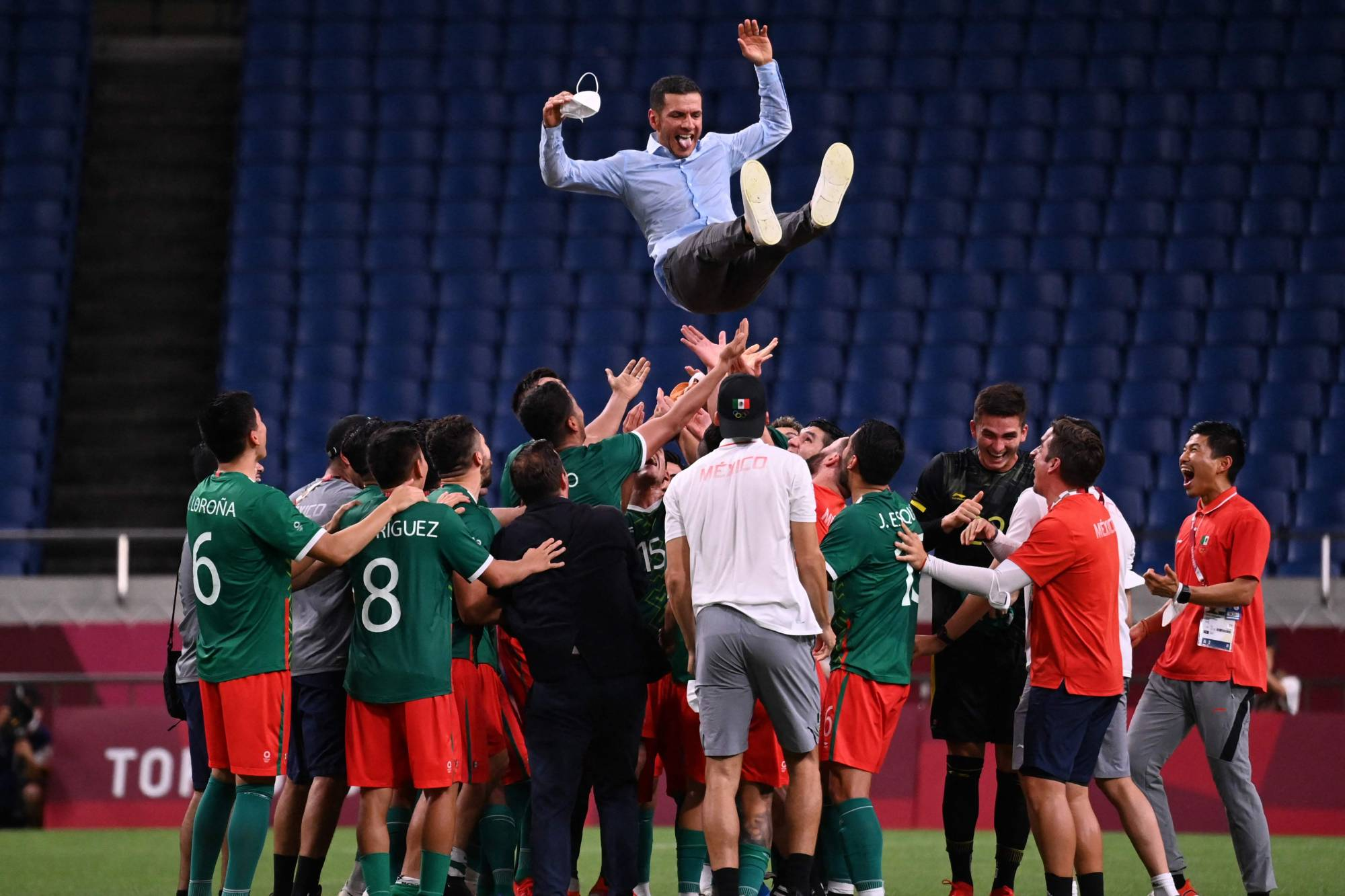 Mexico's players throw coach Jaime Lozano into the air after beating Japan to win the men's bronze medal in soccer. | AFP-JIJI