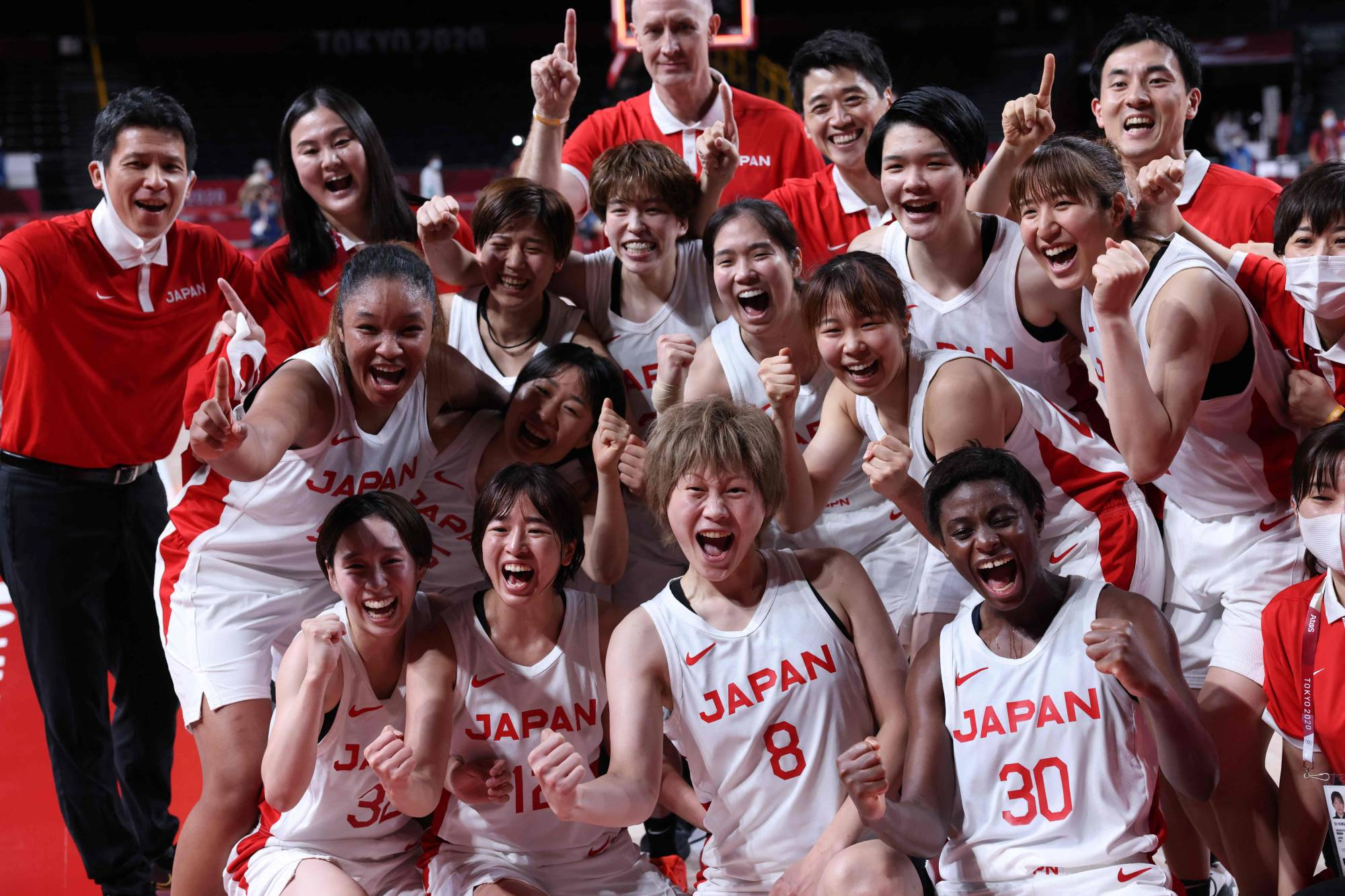 Members of the Japanese women's basketball team pose for a group photo after their win in their semifinal basketball match with France at Saitama Super Arena in Saitama on Friday. | AFP-JIJI