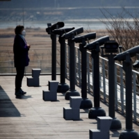 A woman looks toward the north at an observatory platform near the Demilitarized Zone separating the two Koreas in Paju, South Korea, in March.   REUTERS