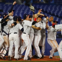 Team Japan celebrates after winning the gold medal game against the U.S. on Saturday at Yokohama Stadium.   REUTERS