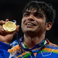 India's Neeraj Chopra holds up his gold medal, the first ever for India, at the victory ceremony for the men's javelin throw event.    AFP-JIJI
