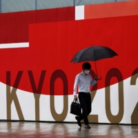 A man wearing a protective face mask walks past a sign for the Tokyo Olympics in the capital on Sunday, the last day of the Games.   REUTERS