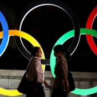 People wearing protective face masks walk past an illuminated Olympic rings monument during the Tokyo Games in the capital on Thursday.   REUTERS