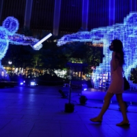 A woman wearing a protective face mask walks past an illuminated decoration featuring the field athletics' relay event during the Tokyo Olympics in the capital on Thursday.   REUTERS