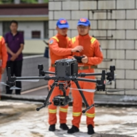 Members of the Yunnan Forest Brigade operate a drone to monitor a herd of migrating elephants at a command center in Daqiao, Yunnan province.  | AFP-JIJI