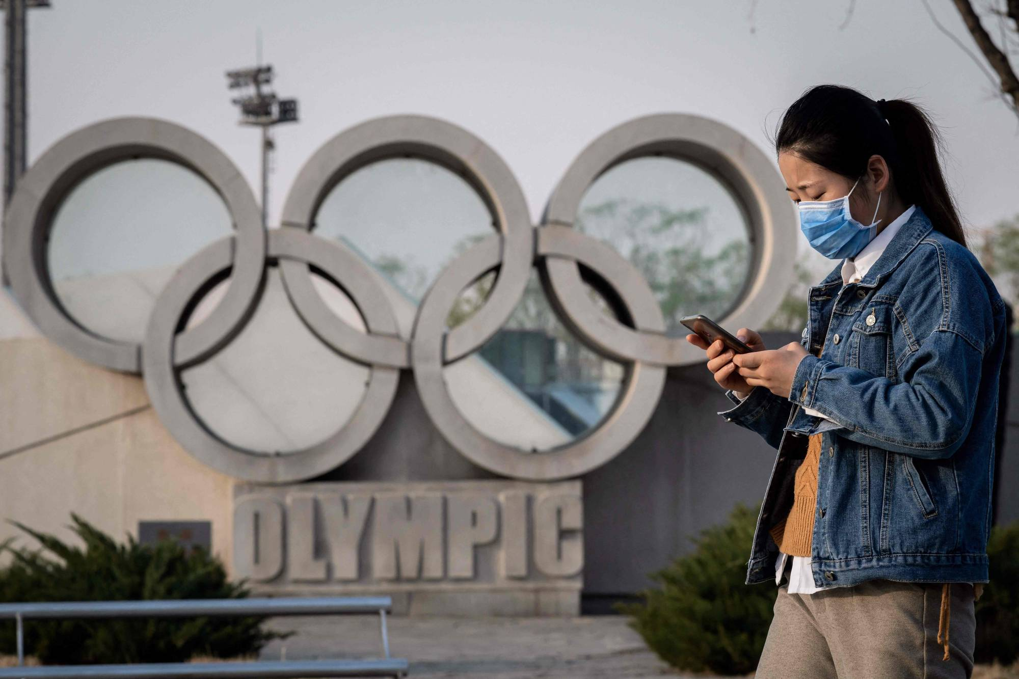 A woman wearing a face mask walks in front of an Olympic rings sculpture at Beijing's 'Birds Nest' National Stadium, the main site of the 2008 Beijing Olympics, in March last year. | AFP-JIJI