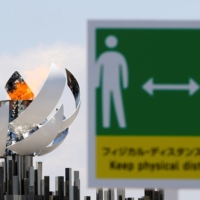 The second Olympic flame cauldron is seen next to a signboard advising visitors to maintain social distance at Ariake Yume-no-Ohashi Bridge, on July 24, a day after the official opening of Tokyo Olympics. | REUTERS