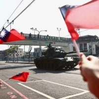 People wave Taiwan's flag while tanks pass on a street during a military drill in Taichung, Taiwan, in November 2020. | REUTERS