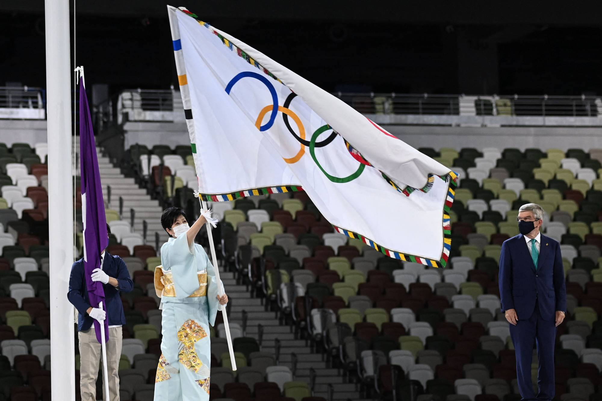Tokyo's governor Yuriko Koike hold the Olympic flag during the closing ceremony of the Tokyo 2020 Olympic Games | AFP-JIJI
