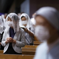 Worshipers pray during a Mass marking the 76th anniversary of the atomic bombing of Nagasaki, at Urakami Cathedral in the theater early Monday. | KYODO