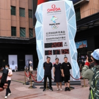People pose for pictures in front of a countdown clock in the Chinese capital marking 200 days until the start of the Beijing Games, on July 19.   REUTERS