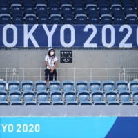 An Olympic staff member watches a women's hockey match amid rows of empty seats at Oi Hockey Stadium in Tokyo on Wednesday. | REUTERS
