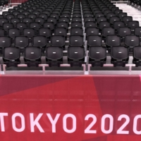 Grandstand seats sit empty during an Olympic men's handball match at Yoyogi National Stadium in Tokyo on July 24. | AFP-JIJI