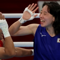 Japan's first female boxing champion at the Olympics, Sena Irie, high-fives Nesthy Petecio of the Philippines. | REUTERS