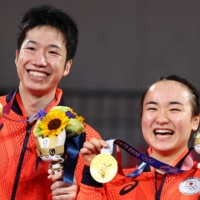 Gold medalists Jun Mizutani and Mima Ito hold up their medals during the victory ceremony of mixed doubles table tennis. | REUTERS