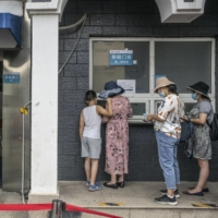 Residents queue at a COVID-19 testing facility in Beijing on Monday.   BLOOMBERG