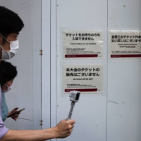 People walk past signs concerning tickets at one of the entrances of the National Stadium ahead of the opening ceremony of the Tokyo Olympics on July 23.   AFP-JIJI