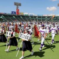 Players march during the opening ceremony of this summer's National High School Baseball Championship at Koshien Stadium in Nishinomiya, Hyogo Prefecture, on Tuesday. | POOL / VIA KYODO