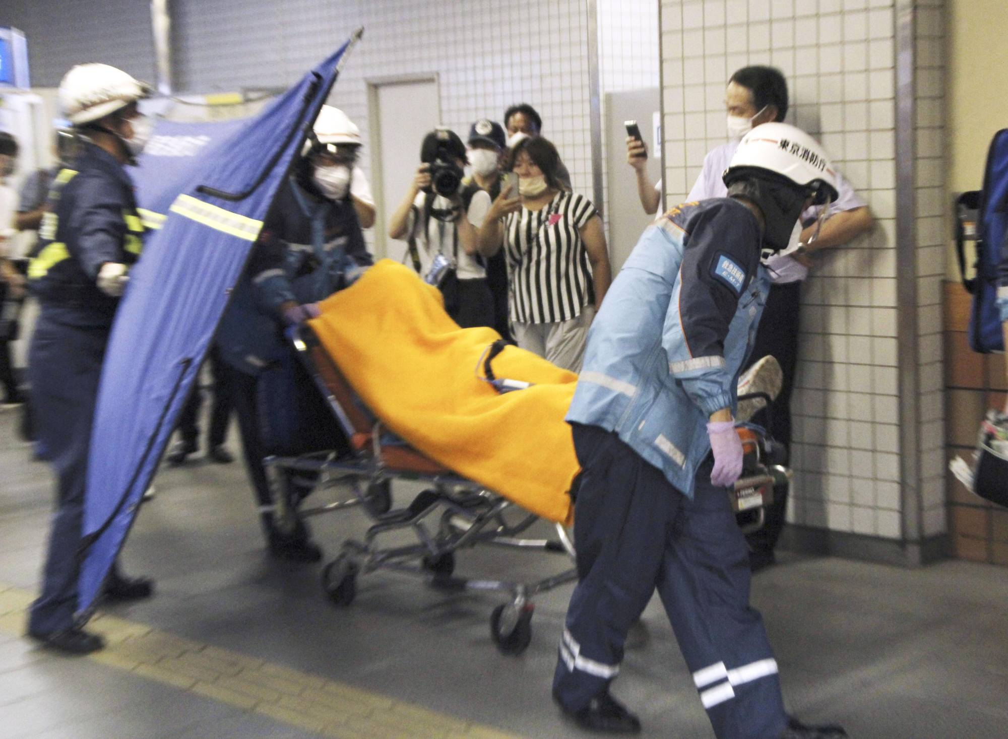 Paramedics carry an injured passenger from an Odakyu Electric Railway train on Friday in Tokyo, after a man went on a stabbing rampage inside the train. | KYODO