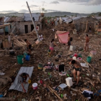Residents bathe, wash and pump water in their destroyed village following damage caused by Typhoon Vamco in Rizal province, the Philippines, in November 2020.  | REUTERS