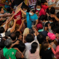 Residents affected by Typhoon Vamco crowd around a group giving away sleeping mats in an evacuation center in Rizal province, the Philippines, in November 2020. | REUTERS