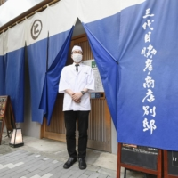 Toshiyuki Fujimura, deputy manager of a grilled meat restaurant in Nagoya, stands in front of the restaurant, which is giving discounts to customers who show proof they have been vaccinated. | KYODO