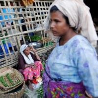 A woman sells food at a camp for displaced Rohingya people outside Sittwe in the state of Rakhine, Myanmar, in 2016. | REUTERS