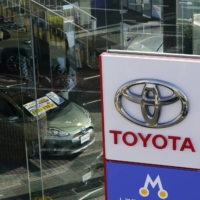 Toyota Motor Corp. reported a record net profit for the April to June quarter but maintained its full-year earnings forecasts, citing three factors including raw material costs.   BLOOMBERG